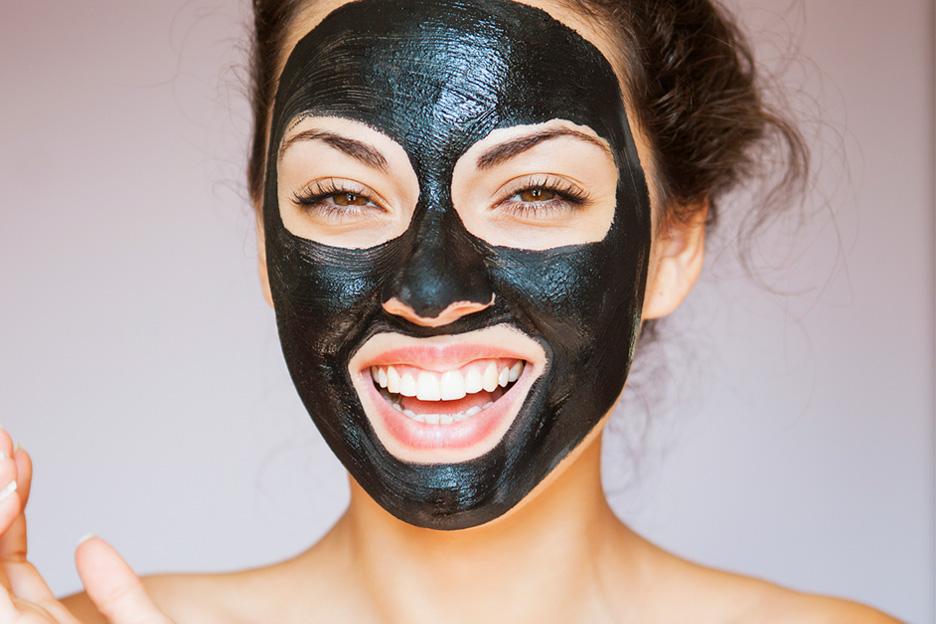 Vrouw met een blad bevochtigend masker op haar gezicht dat